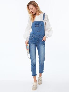 Salopette en jean bleu délavé moyen.