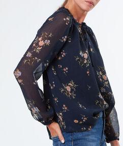 Chemise fleurie nouée au col bleu marine.